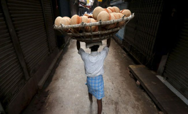 A man carries a basket filled with earthen pots for delivery to a sweet shop through an alley...