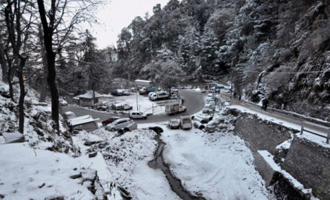 Vechicles move slowly on a road after snowfall in Shimla on Wednesday...