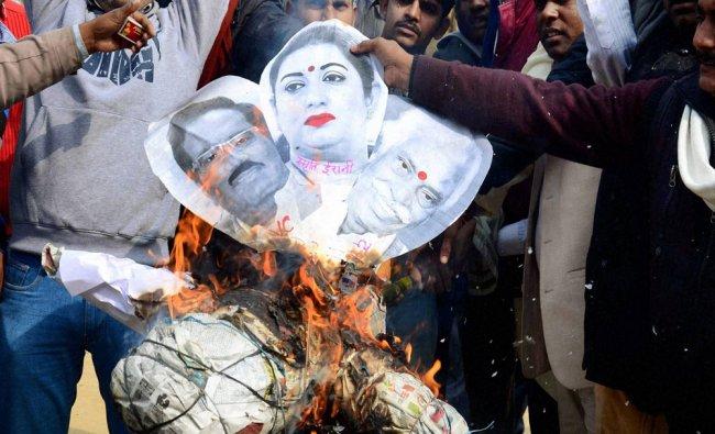 Protestors burn an effigy of HRD Minister Smriti Irani, Union Labour Minister Bandaru Dattatreya...