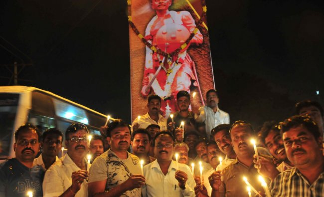 People pay a tribute by lighting the lamp to Sangolli Rayanna during...