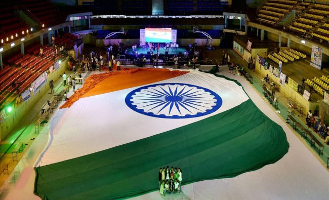 A group of people pose in front of a giant Indian flag as part of \'We Salute India\' event...