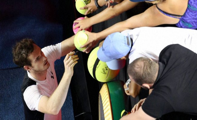 Andy Murray of Britain signs autographs after defeating David Ferrer of Spain...