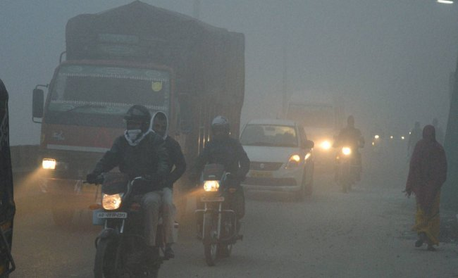 People move at a road during a cold and foggy morning in Gurgaon...