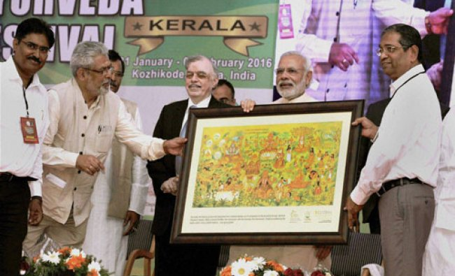 Prime Minister Narendra Modi is presented with a memento at the Global Ayurveda Festival in Kozhi..