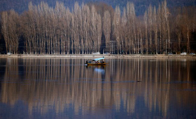 People row a boat in the waters of Dal Lake on a sunny winter day in Srinagar...