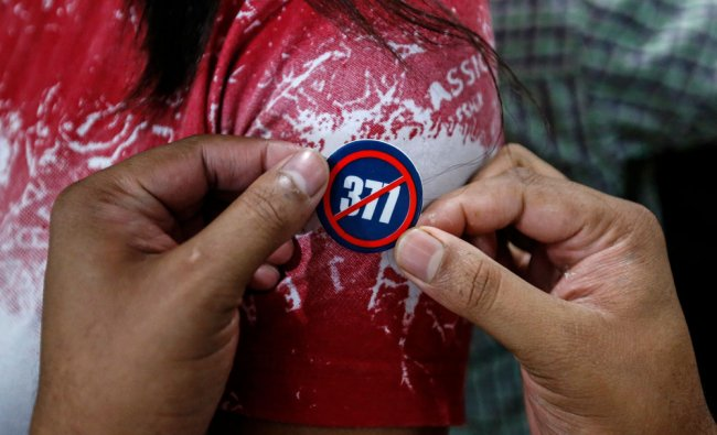 A gay rights activist pins a badge onto another during a gathering in Mumbai...