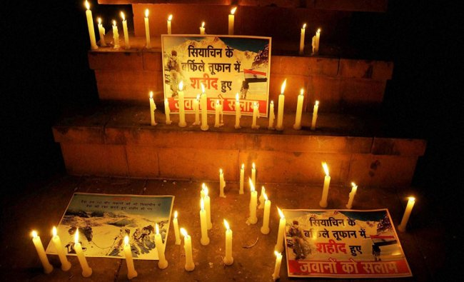 People light candles to paying tributes to ten soldiers who died in...