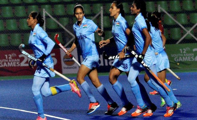 Women Indian hockey players (blue )celebrate after scoring a goal against Srilanka (red ) during...