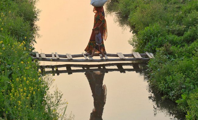 A woman holds the hand of a boy as they cross a temporary bridge made of bamboo on a canal...