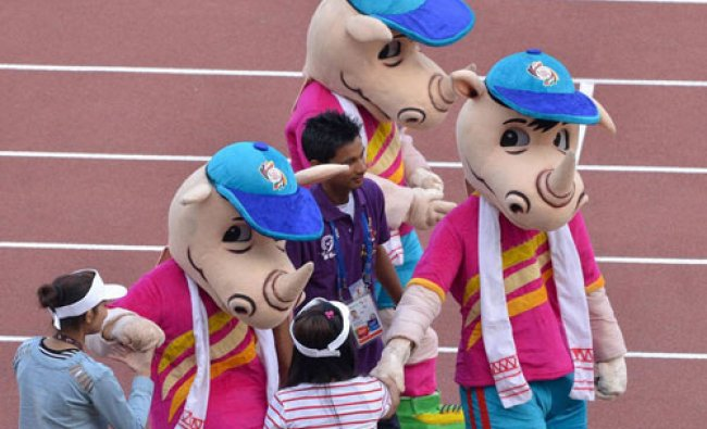 Volunteers shake hands with the official mascot of the 12th South Asian Games, Tikhor...