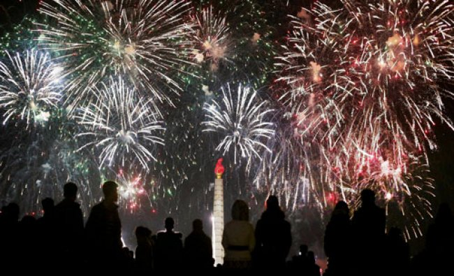 North Koreans watch from the Kim Il Sung Square as fireworks explode over the Juche Tower ...
