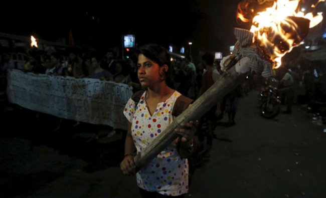 A student holds a torch during a rally to protest against the arrest of a student of JNU...