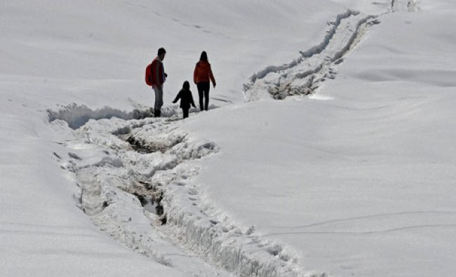 A tourist couple with their kid at Gulmarg ski resort in district Baramulla...