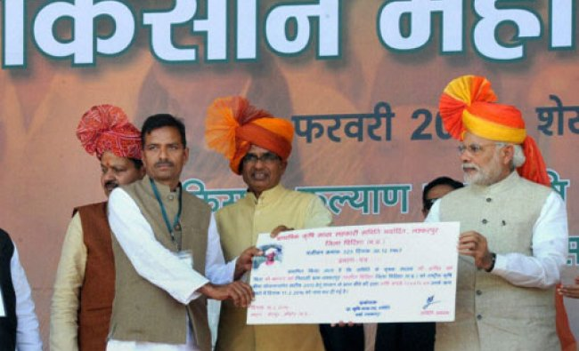 Prime Minister Narendra Modi presenting settlement claims of Kharif 2015 crop insurance to a...