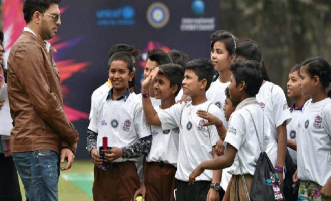 Cricketer Yuvraj Singh interacts with the children at the launch of Team Swachh clinics, an...
