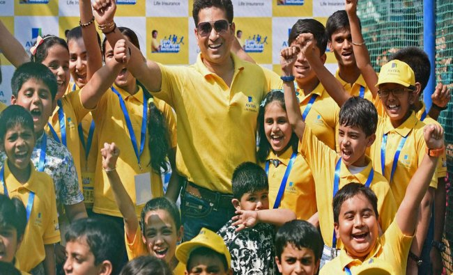 SachinTendulkar with kids during a promotional event of Aviva Life Insurance...