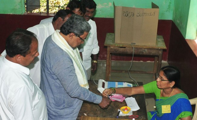 Election official inks Chief Minister Siddaramaiah\'s fingers during Zilla and Taluka Panchayath...