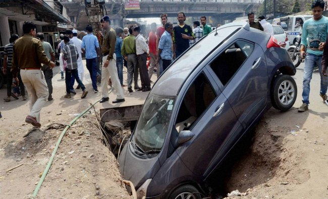 People looking at a car that fell into a roadside ditch in Bhopal on Saturday...
