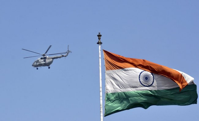An Air Force helicopter flies past an Indian national flag over Rohtak...