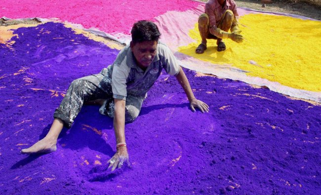 Workers drying up colored powder (Gulal) ahead of Holi festival...