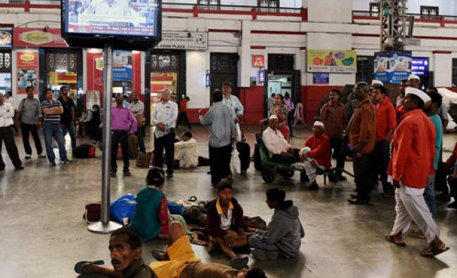Railway porters watch the union railway budget being announced on a display screen at Mumbai ...
