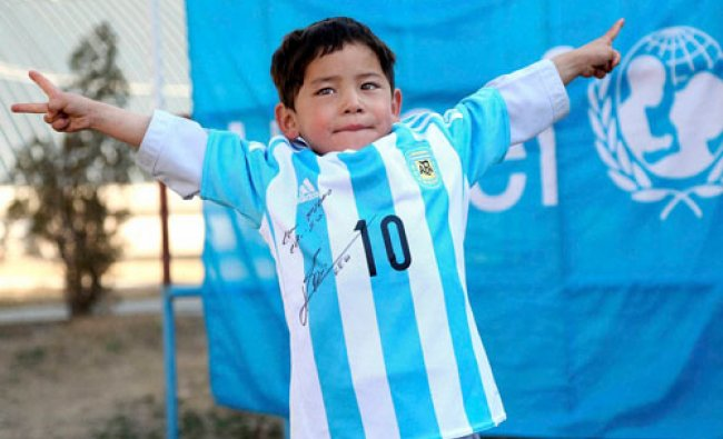 In this provided by UNICEF, Murtaza Ahmadi, an Afghan Lionel Messi fan, shows a donated and signed..