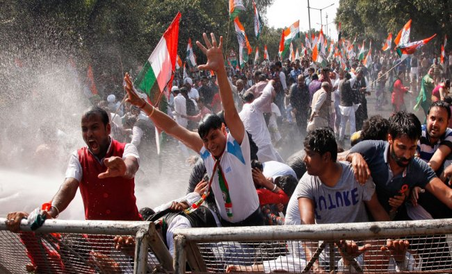 Members of Cong party shout slogans as police use a water cannon to disperse them during protest...