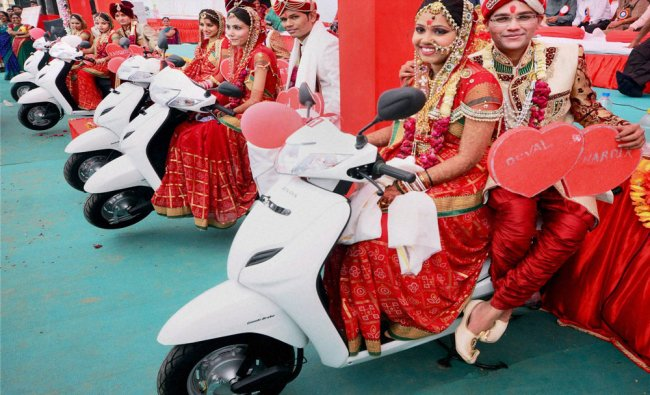Couples pose with scooters given to them during Patel community mass marriage in Ahmedabad...