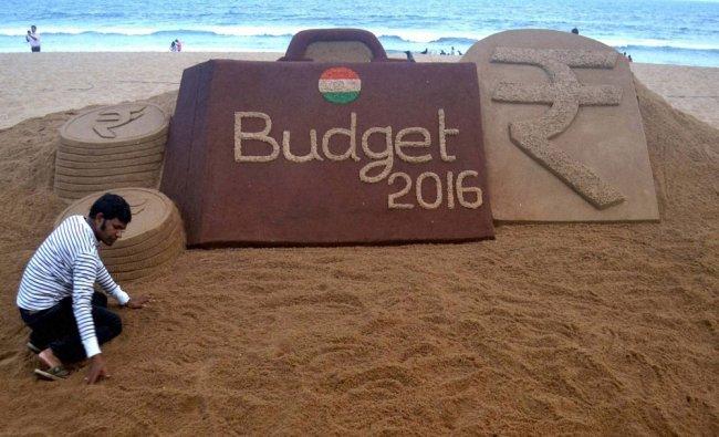 Sand artist Sudarsan Pattnaik makes a sand sculpture on upcoming Budget 2016 at Puri...