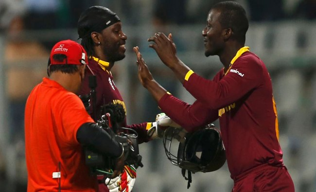 Chris Gayle (C) is congratulated by his captain Darren Sammy (R) after winning their match...