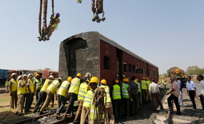 Rescue workers push a passenger coach on a track during a mock rescue drill...