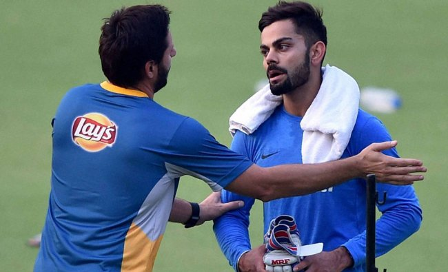 Shahid Afridi interacts with Virat Kohli during their training session at the Eden Gardens...