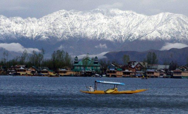 A shikara sails at Dal Lake with snow covered Zabarwan mountains and heavy clouds...