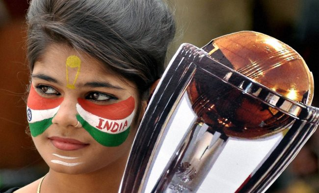 A fan of Indian cricket team with face painted in tricolor holds a replica of WC trophy...