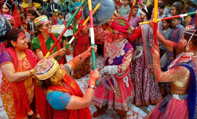 Devotees celebrate latthmar Holi at Varshaney Mandir in Aligarh..