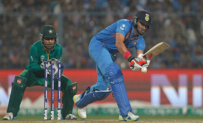 India\'s Yuvraj Singh (R) plays a shot as Pakistan\'s wicketkeeper Sarfraz Ahmed looks on...