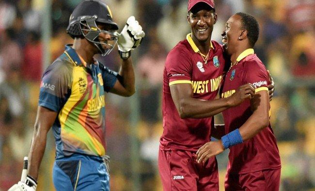 West Indies bowler Dwayne Bravo with Darren Sammy celebrates the wicket of Angelo Mathews of Sri...