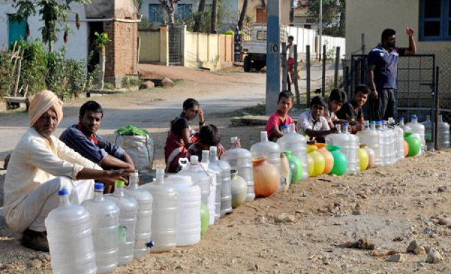 Villagers wait to collect drinking water under Shudh Ganga project in a drought-hit area near ....