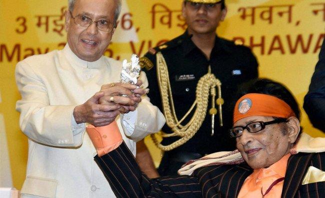 Pranab Mukherjee shows a silver statue of Sai Baba gifted to him by veteran actor Manoj Kumar...