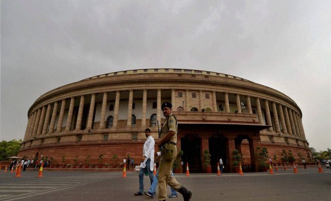 A security person walks as clouds hover over the Parliament house during the Parliament session...