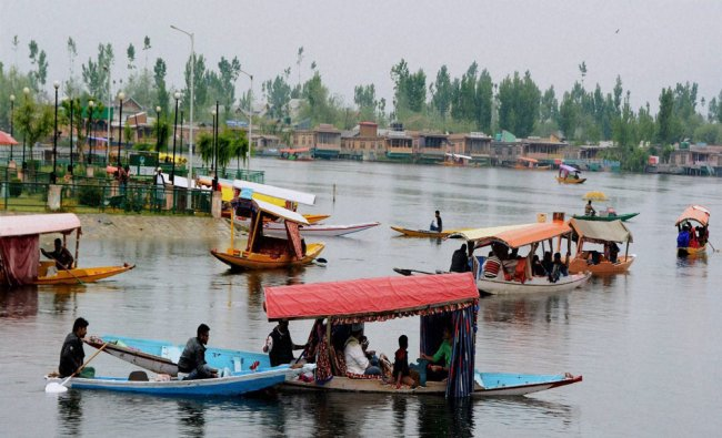 Tourists ride Shikaras as they enjoy the cool weather at Dal Lake in Srinagar...