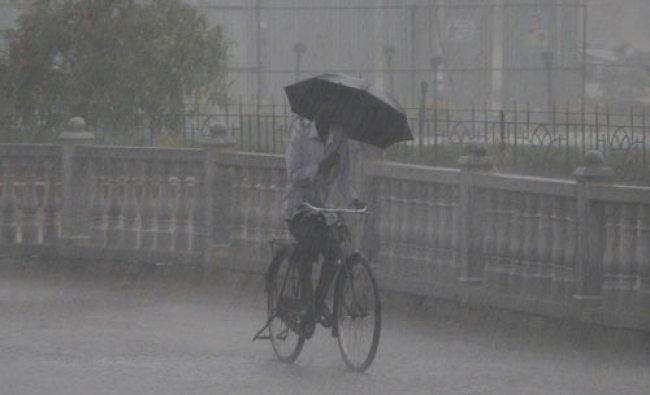 A Bicycle rider are struggle to move in water logged road at K R Circle during the heavy rain in...