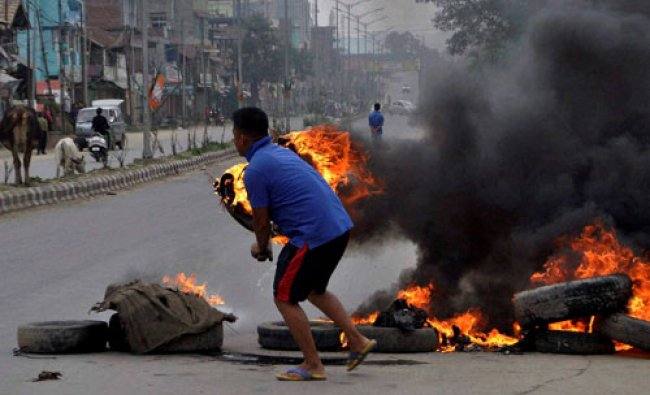 A youth blocks a road during a public curfew called by the Joint Committee on Inner Line Permit...