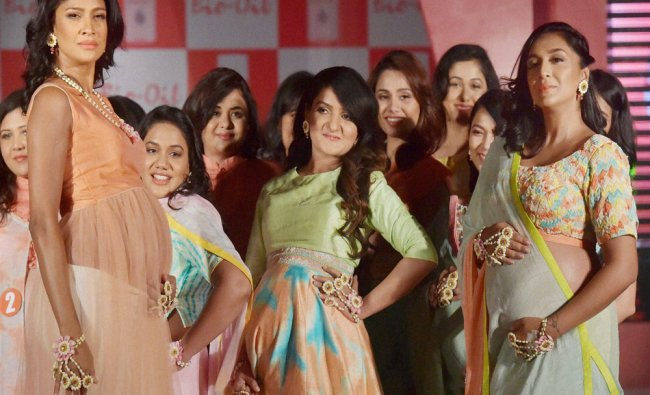 Pregnant models walk the ramp on the eve of mother day in Mumbai...