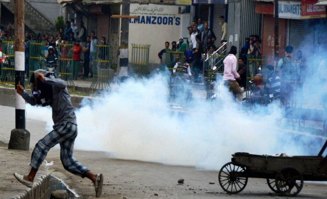 Youth run for cover amid tear gas smoke fired by the police during a clash at Saraf Kadal...