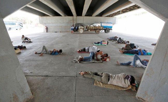 People sleep under a bridge on a hot summer day in Ahmedabad, India...