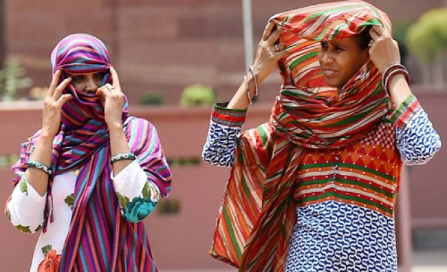 Women protect themselves on hot day in New Delhi on Sunday...