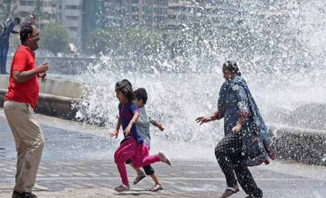 People enjoy a high tide at the Marine drive in Mumbai on Sunday....