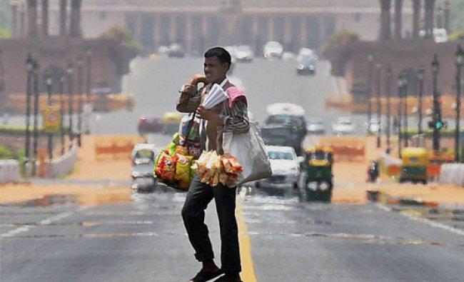 A street vendor crosses road on the Rajpath as the mercury rises in New Delhi...