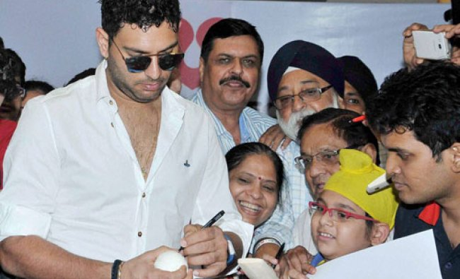 Yuvraj Singh gives autographs to his fans during an event in Kolkata...